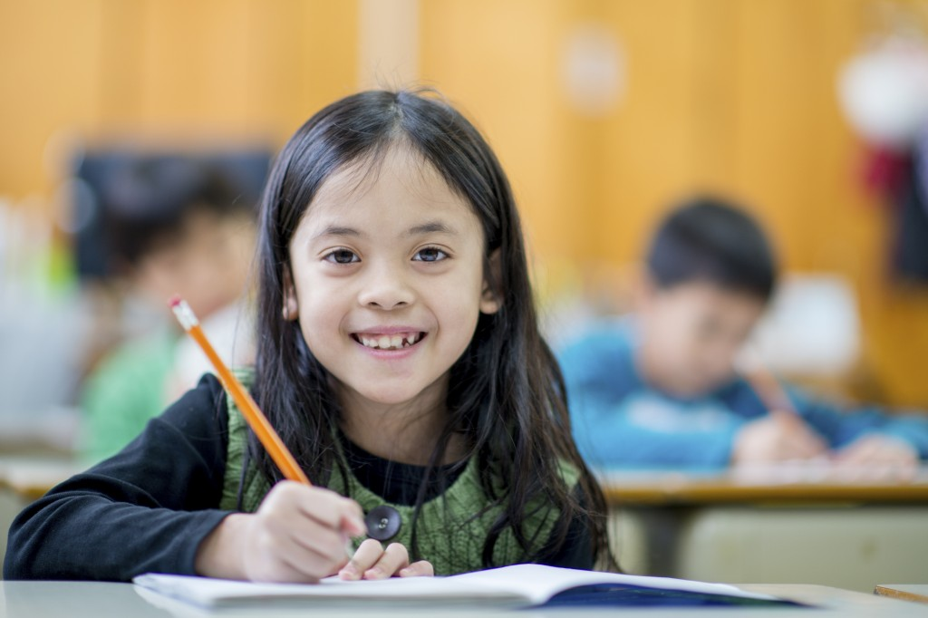 A multi-ethnic group of elementary age children are sitting at their desks and are writing in their notebook for an in class assignment. One girl is smiling while looking at the camera.